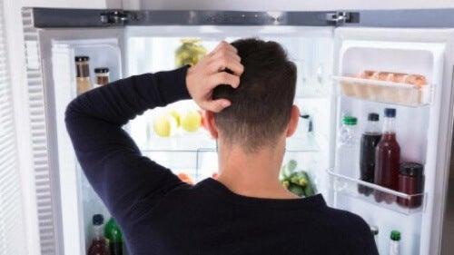 Uomo davanti al frigorifero aperto.