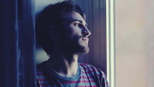 Ragazzo triste e pensieroso che guarda dalla finestra.