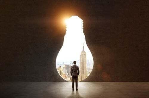 Uomo di fronte a una porta sul mondo a forma di lampadina.