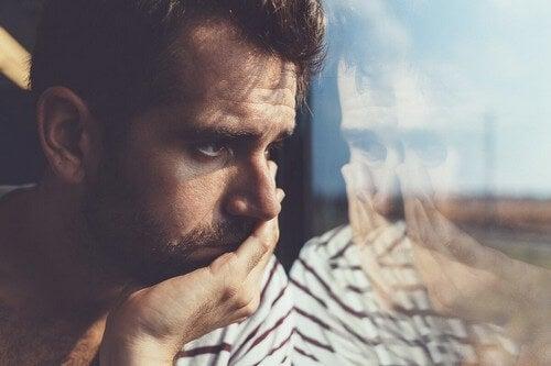 Uomo pensieroso che guarda dalla finestra.