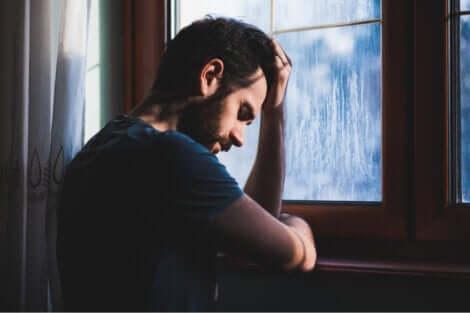 Uomo triste alla finestra.