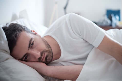 Uomo triste e pensieroso sdraiato nel letto.