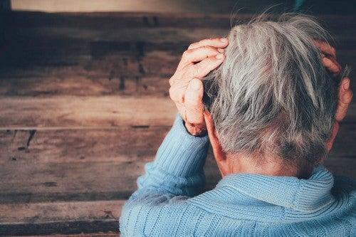 Anziana confusa che tiene la testa tra le mani.