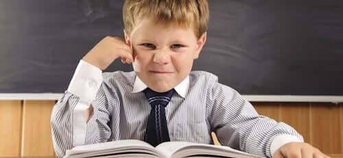 Bambino adirato perché deve leggere un libro.