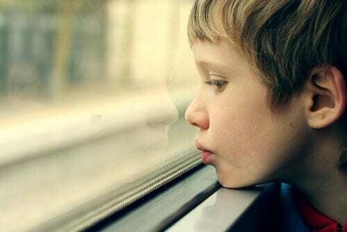 La neurobiologia del trauma e bambino autistico che guarda fuori dalla finestra.