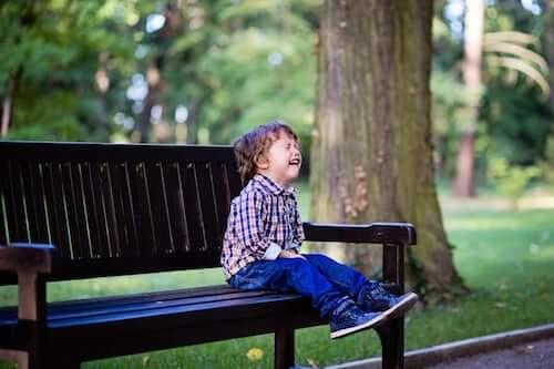 Bambino che piange seduto su una panchina in un parco.