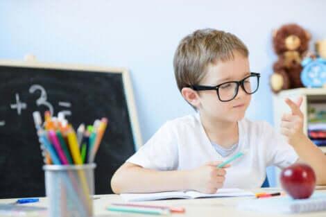 Bambino seduto al banco fa i calcoli con la mano.
