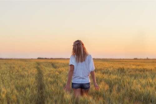Donna di spalle in un campo di grano.