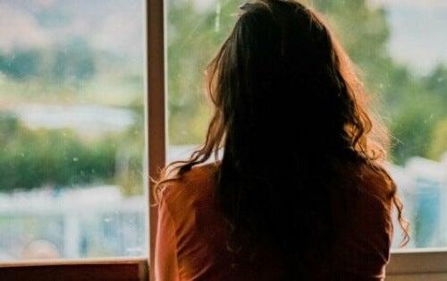 Donna che guarda fuori dalla finestra.