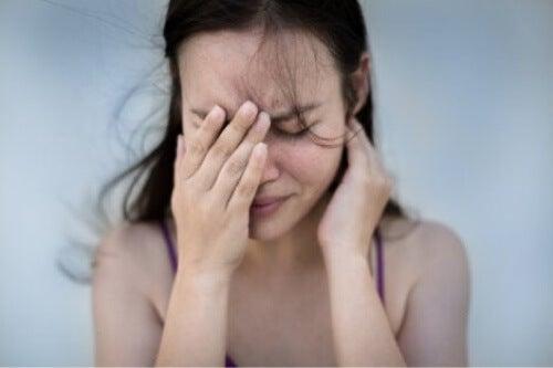 Donna con attacco di cefalea.