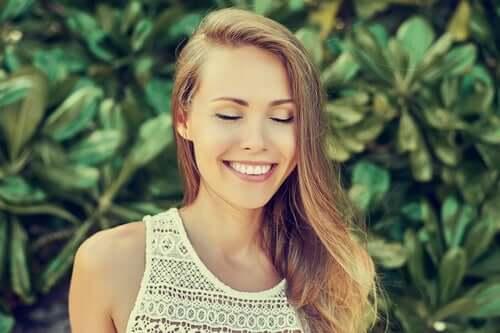 Donna con gli occhi chiusi che sorride perché sa come vivere pienamente.