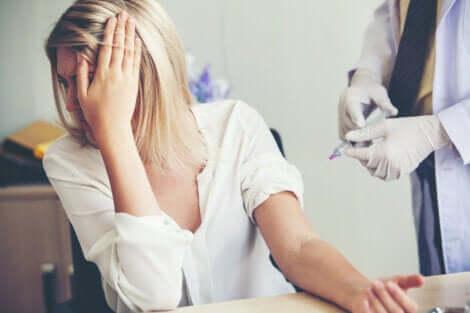 Donna si copre il volto durante iniezione perché soffre di tripanofobia.