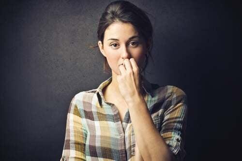 Donna dubbiosa che si mangia le unghie.