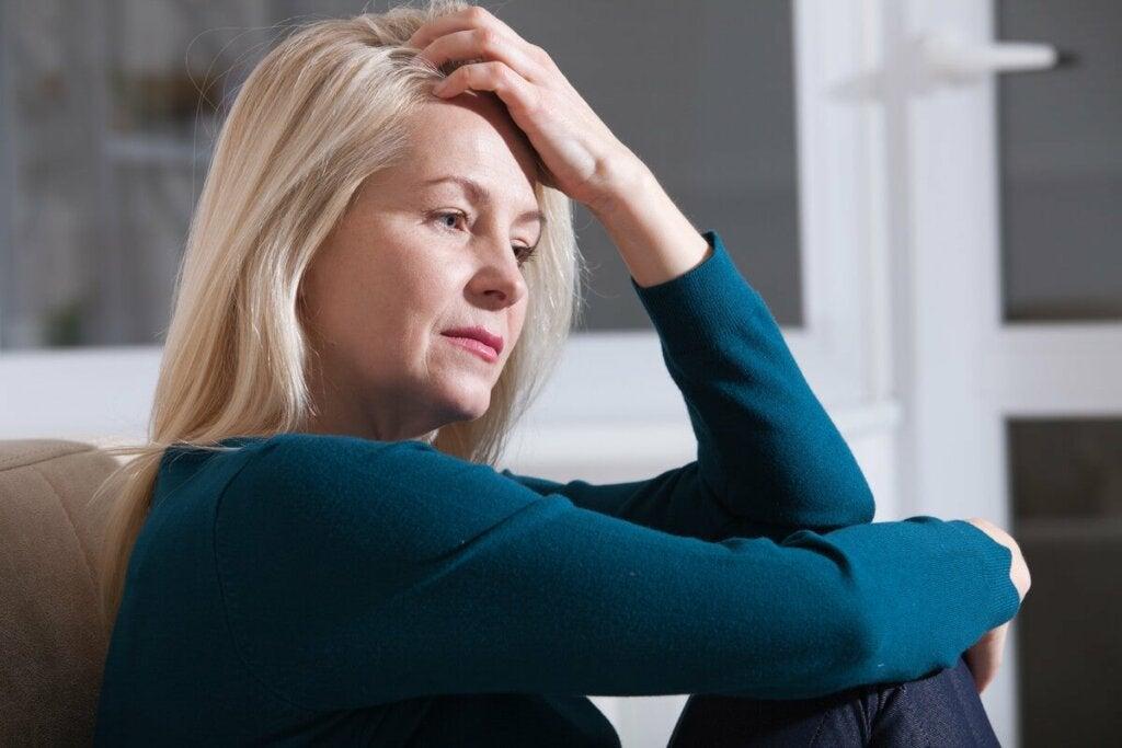 Donna stressata seduta sul divano.