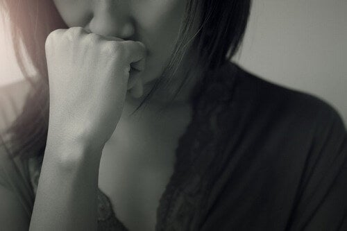 Donna triste con mano sulla bocca.