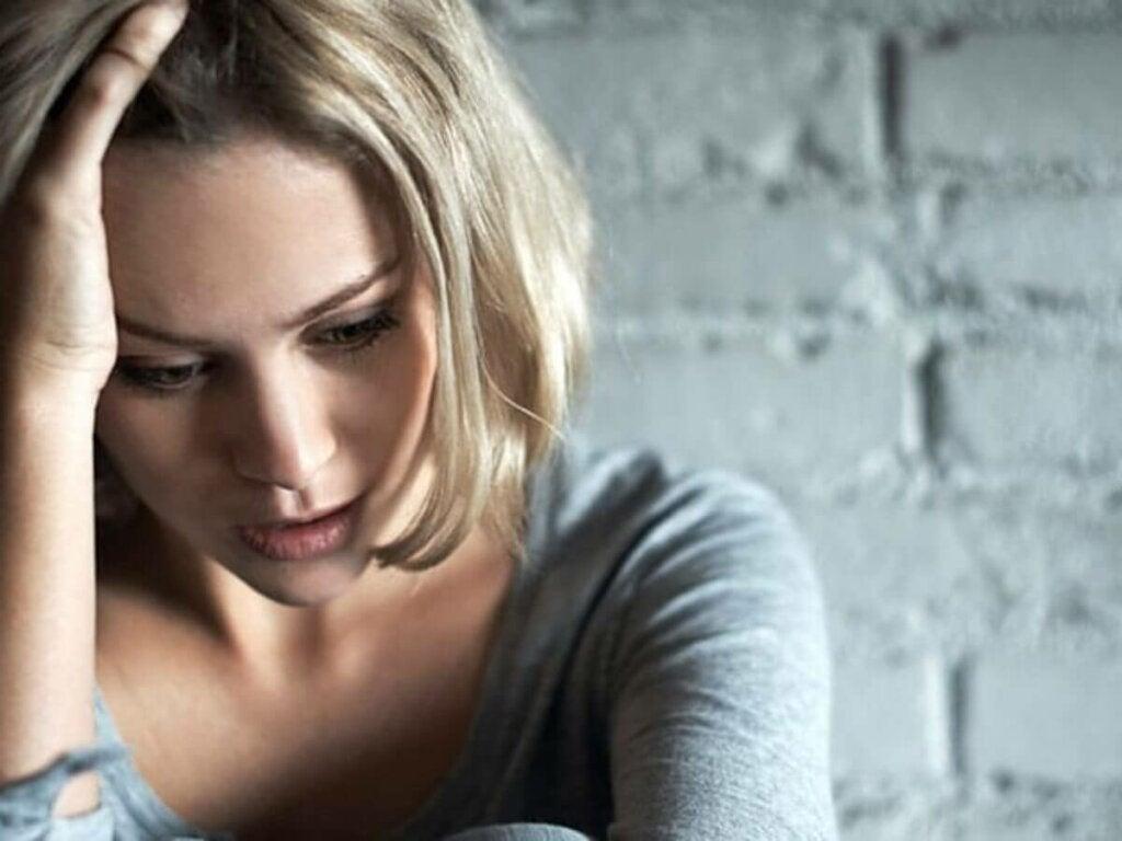 Donna triste con mano sui capelli.