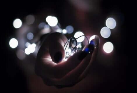 Mano femminile con lucine nel palmo.