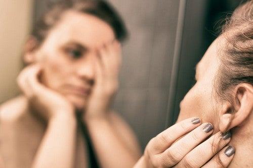 Donna che si guarda allo specchio e inizia a sentirsi a disagio con il proprio corpo.