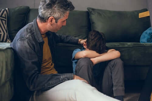 Padre che consola il figlio triste.