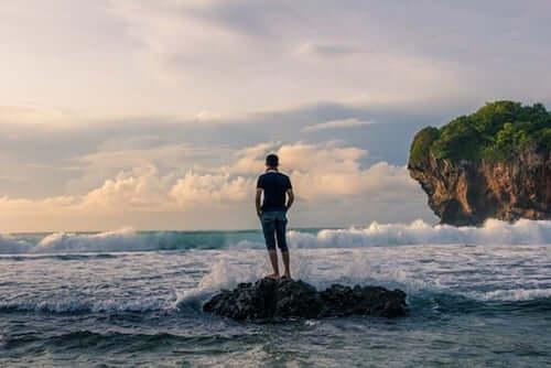 Ragazzo che guarda il mare da uno scoglio.