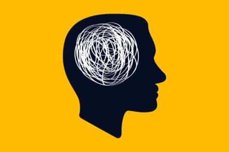 Testa di profilo con groviglio di filo al posto del cervello.