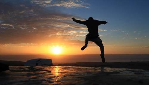 Ragazzo che fa un salto al tramonto.