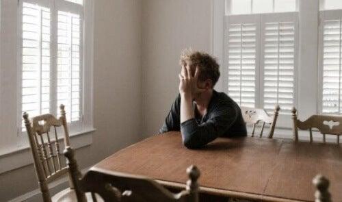 Ragazzo esausto poggiato a un tavolo.