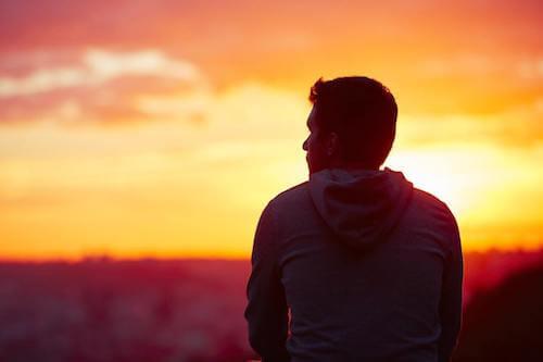 Uomo pensieroso che guarda un tramonto.