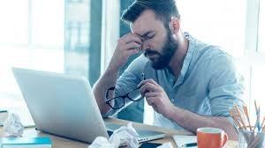 Uomo con mal di testa davanti al computer.