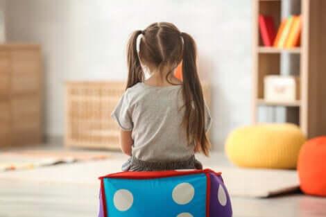 Bambina seduta di spalle sopra un cubo gonfiabile.