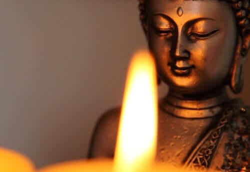 Statuetta del Buddha illuminata da una candela.
