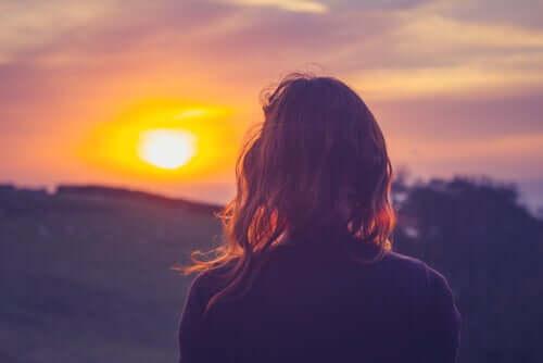 Donna di spalle che guarda il tramonto.