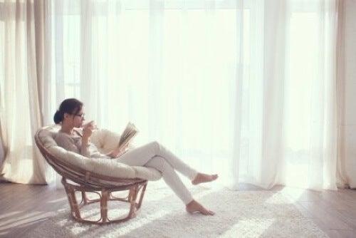 Donna che legge su una poltrona.