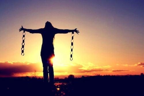 Donna libera dalle catene che apre le braccia al mondo.