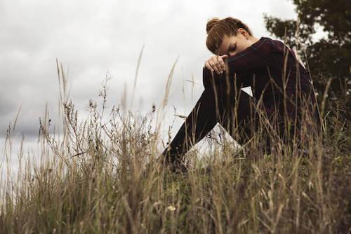 Donna triste che pensa da sola in un parco.