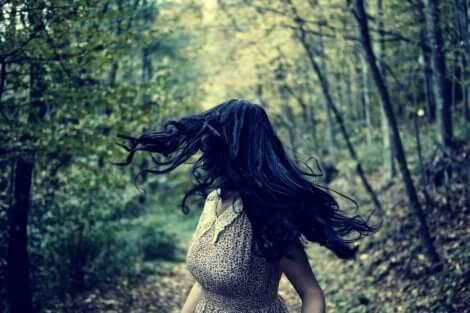 Donna che corre nel bosco.