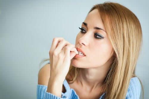 Donna che si mangia le unghie.
