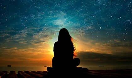 Ragazza seduta di spalle davanti al cielo stellato.