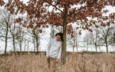Ragazzo appoggiato al tronco di un albero.