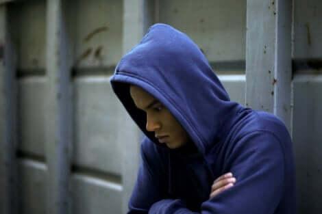 Ragazzo pensieroso che indossa una felpa blu con cappuccio.