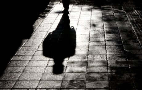 Ombra di uomo che cammina in un vicolo buio.