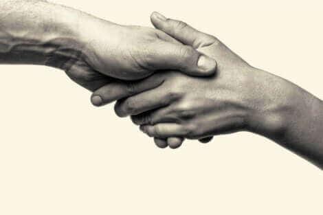 Aiutiamo per empatia? Mani che si stringono.