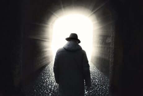 Uomo di spalle si incammina verso la luce.