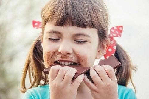Bambina che mangia il cioccolato.