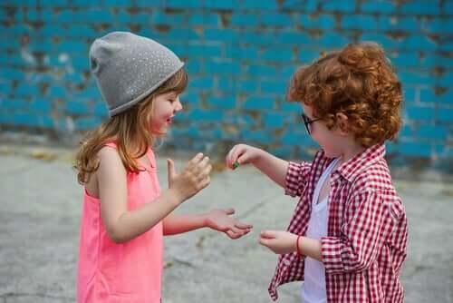 Bambino che regala una caramella ad una sua amica.