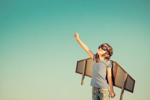 Bambino con aereo di cartone.
