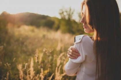 Cercare l'approvazione degli altri, donna abbraccia se stessa.