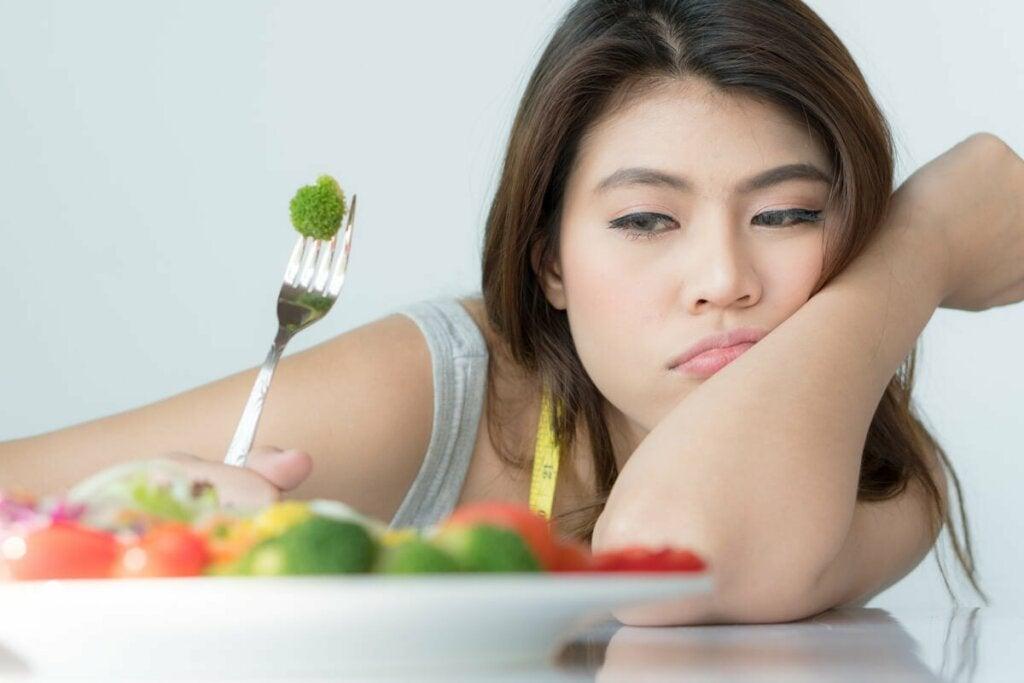 Donna con fobie alimentari che cerca di mangiare le verdure.