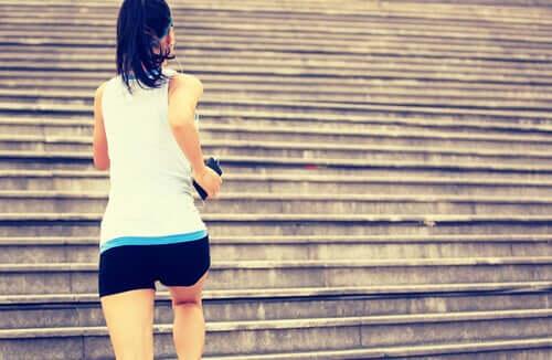 Donna che fa esercizio fisico salendo una rampa di scale.