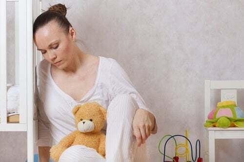 Donna triste che si appoggia su una culla.